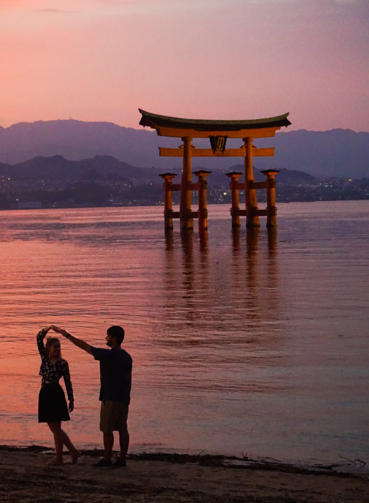 Woman being twirled by a man (dancing) in front of a orange torii gate (shrine) at sunset. A beautiful view on a day trip to Miyajima Island.