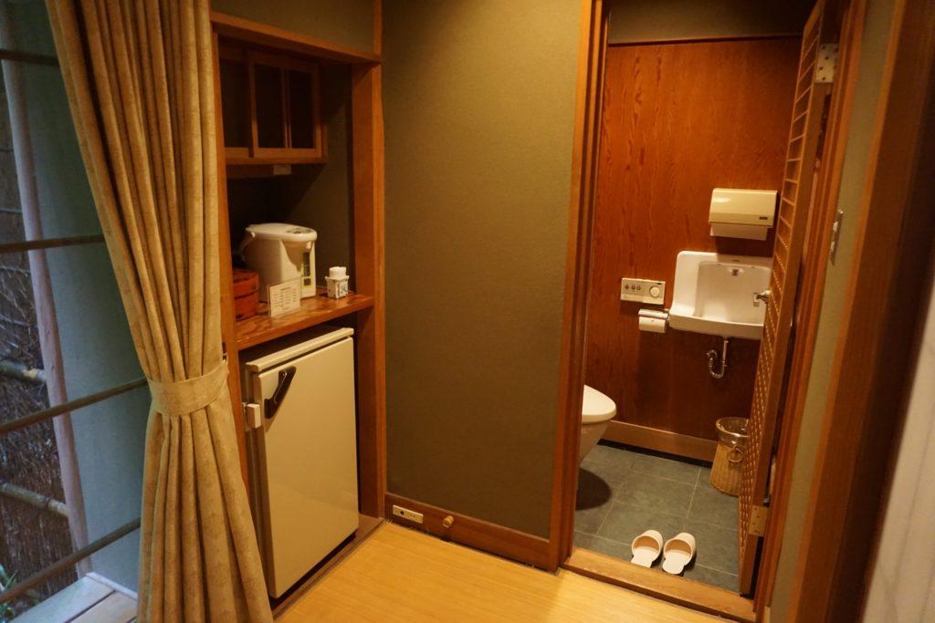 Small kitchenette area and mini fridge next to the toilet area of the Hatsune Room at Nishimuraya Honkan