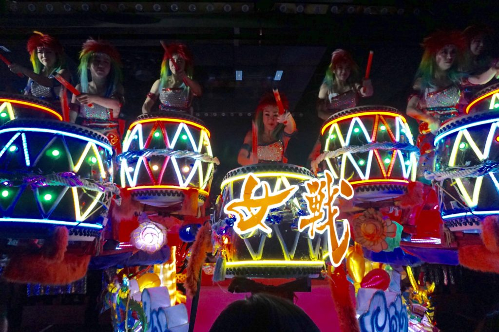 Girls playing drums that are lit up in multiple colors at the Robot Restaurant