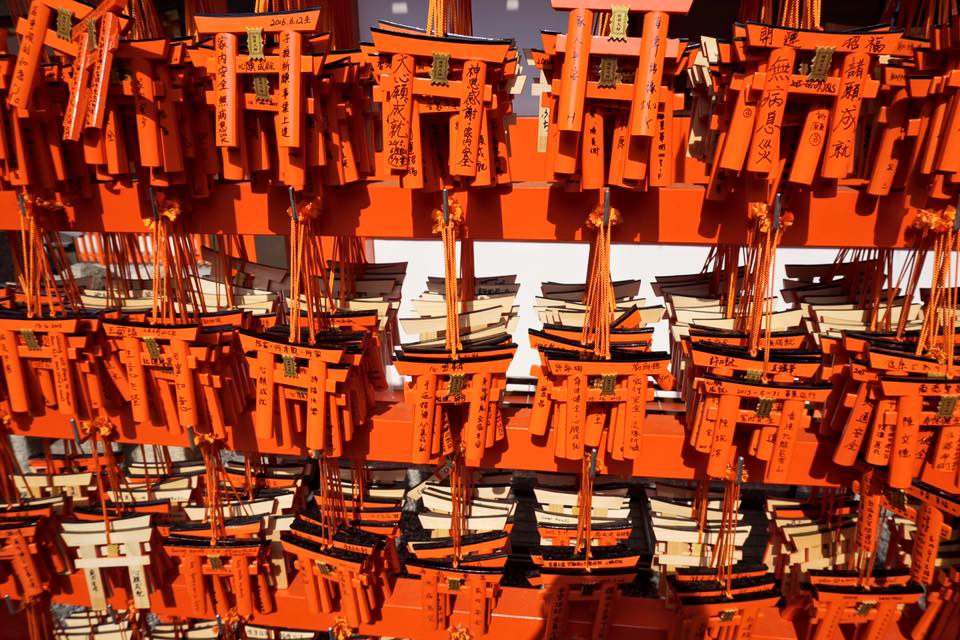 Small orange torii gates with wishes written on them at Fushimi Inari Shrine