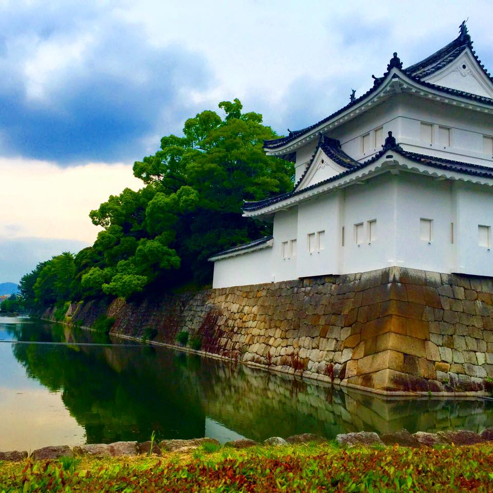 Side view of a white Japanese castle with a water moat around it. (Nijo Castle - Kyoto, Japan)