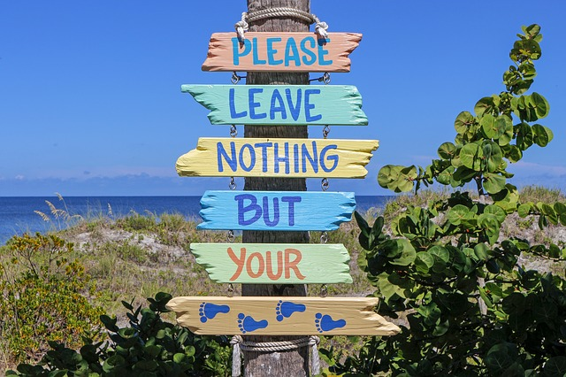"Beach sign that says ""please leave nothing but your footprints."" 