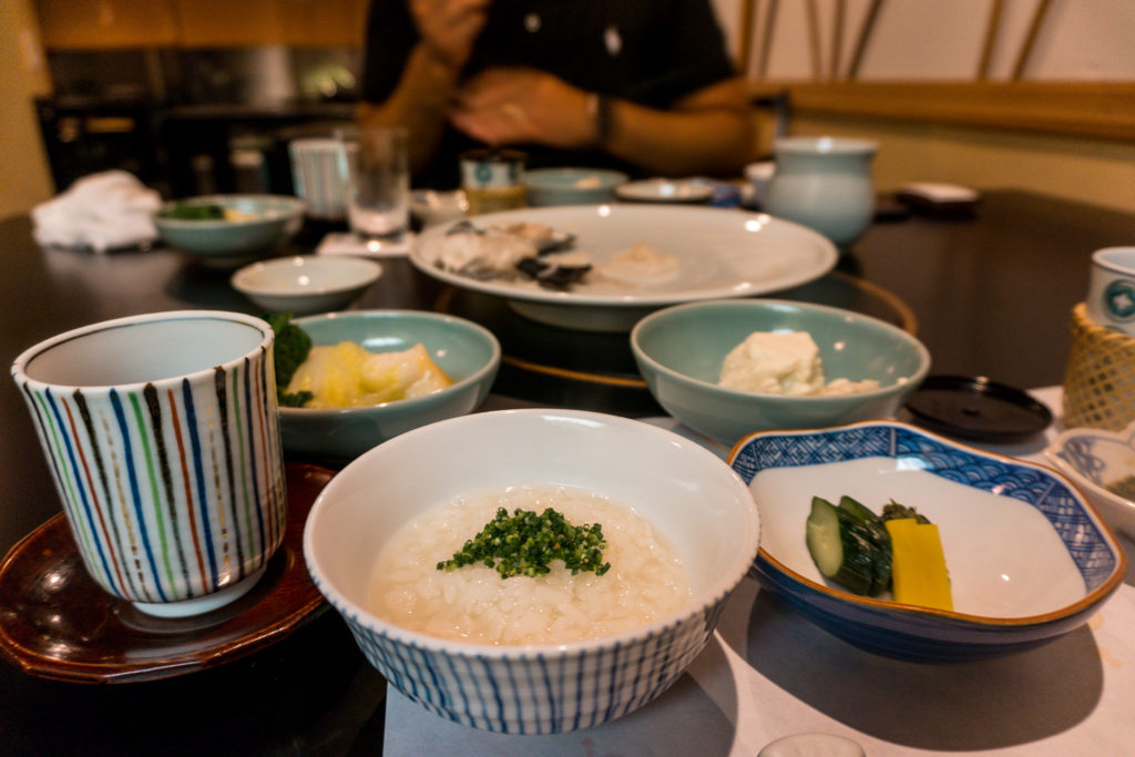 Bowls of rice, vegetables, and blowfish (fugu) hot pot at Hakata Izumi in Fukuoka, Japan