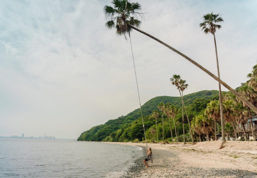 Woman swinging on a swing tied to a palm tree at Nokonoshima Island - Fukuoka