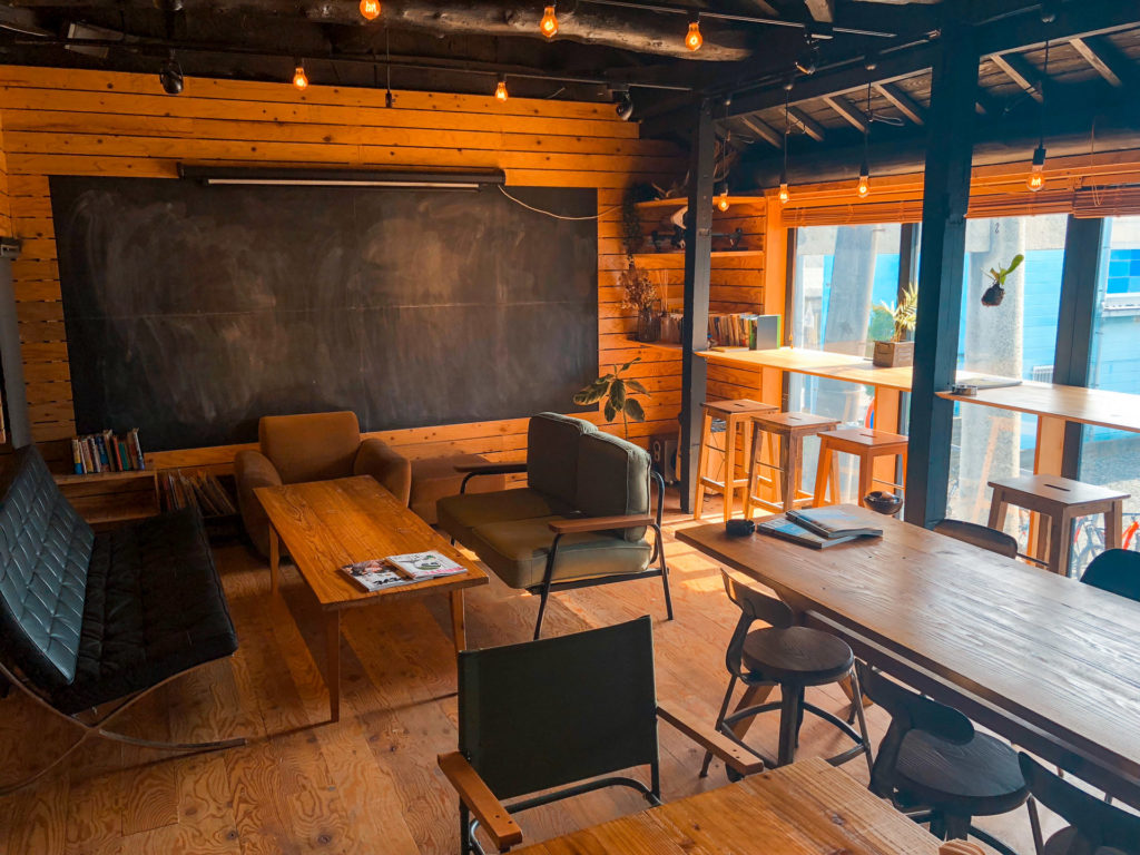 Seating area with couches, a wooden coffee table, and a chalkboard at Shikashima Cycle