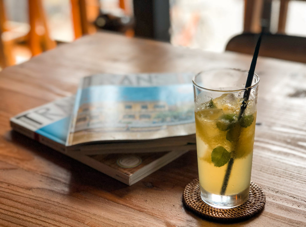Table with a cold beverage in a glass. In the background are two magazines stacked.