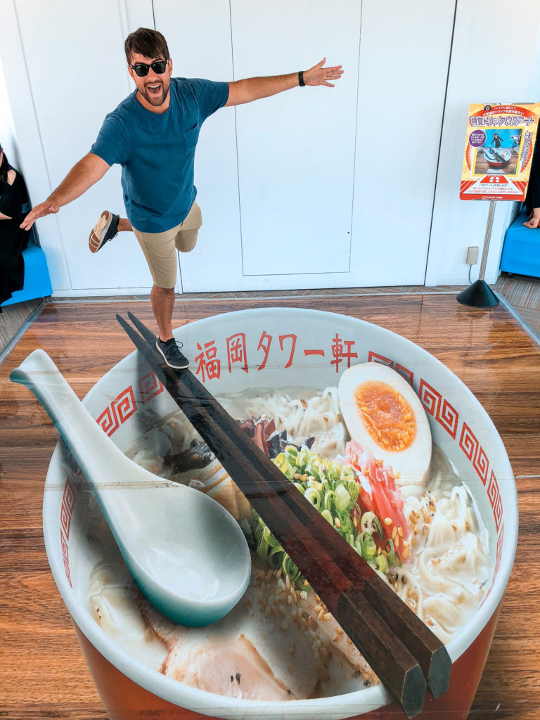 Man standing over a large display of ramen and pretending to balance on faux chopsticks at Fukuoka Tower.