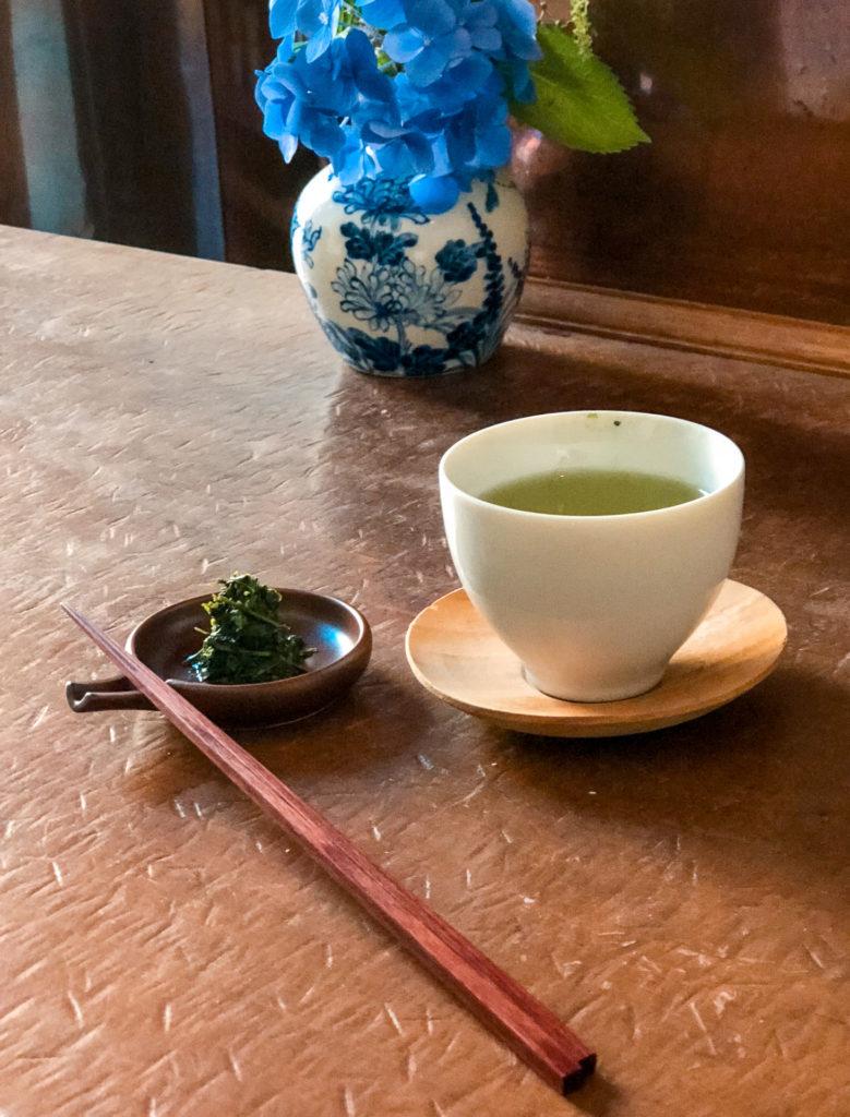 A glass of tea and a plate with tea leaves from YOROZU - Fukuoka