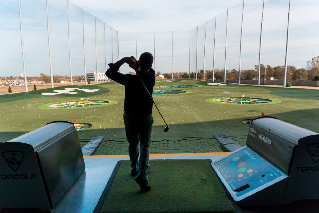 Golf swing at TopGolf Oklahoma City - couples getaway in Oklahoma