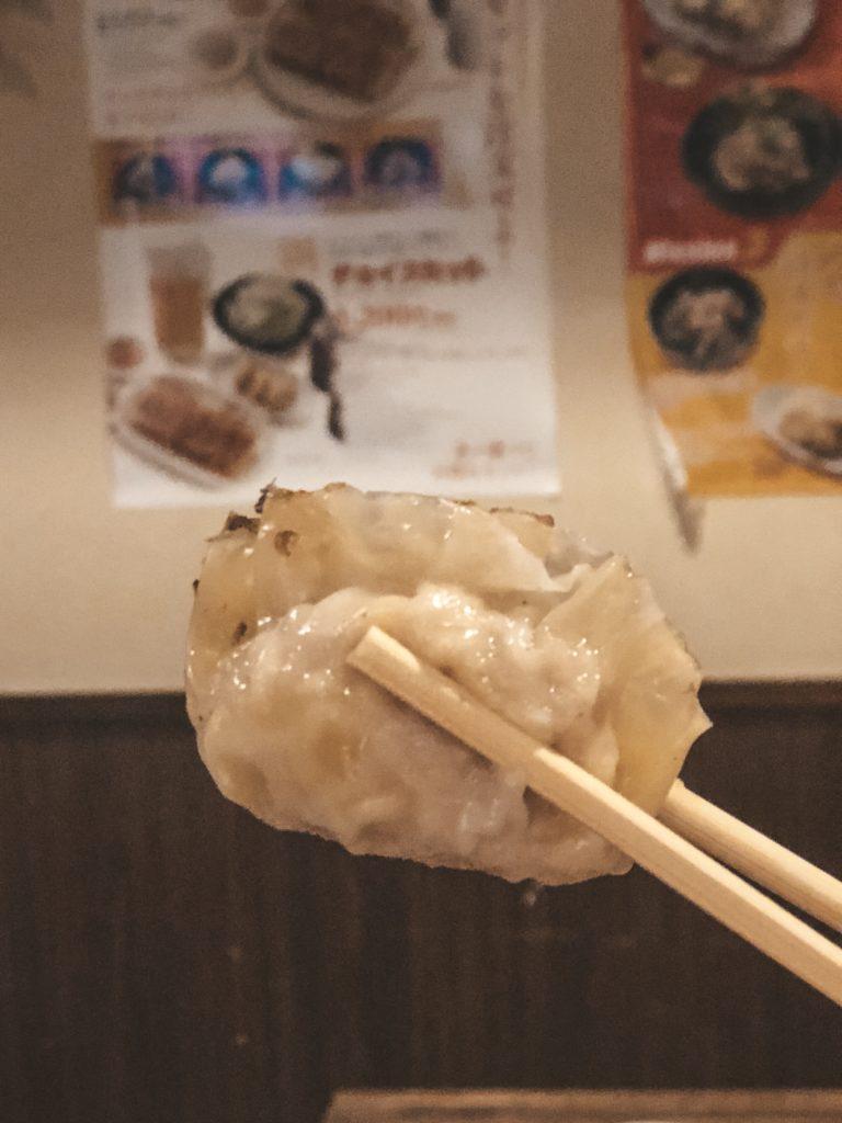Chopsticks holding a pan-fried gyoza from Chao Chao Gyoza in Kyoto, Japan