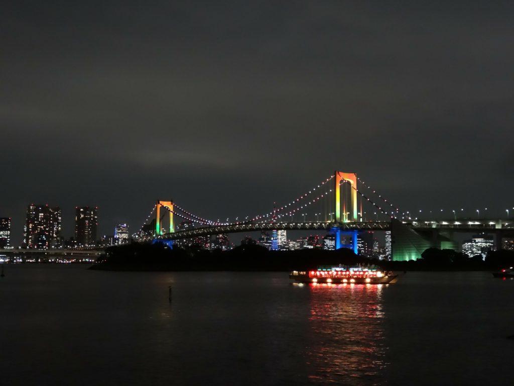A bridge at night with rainbow lights on it (Rainbow Bridge Odaiba in Tokyo)