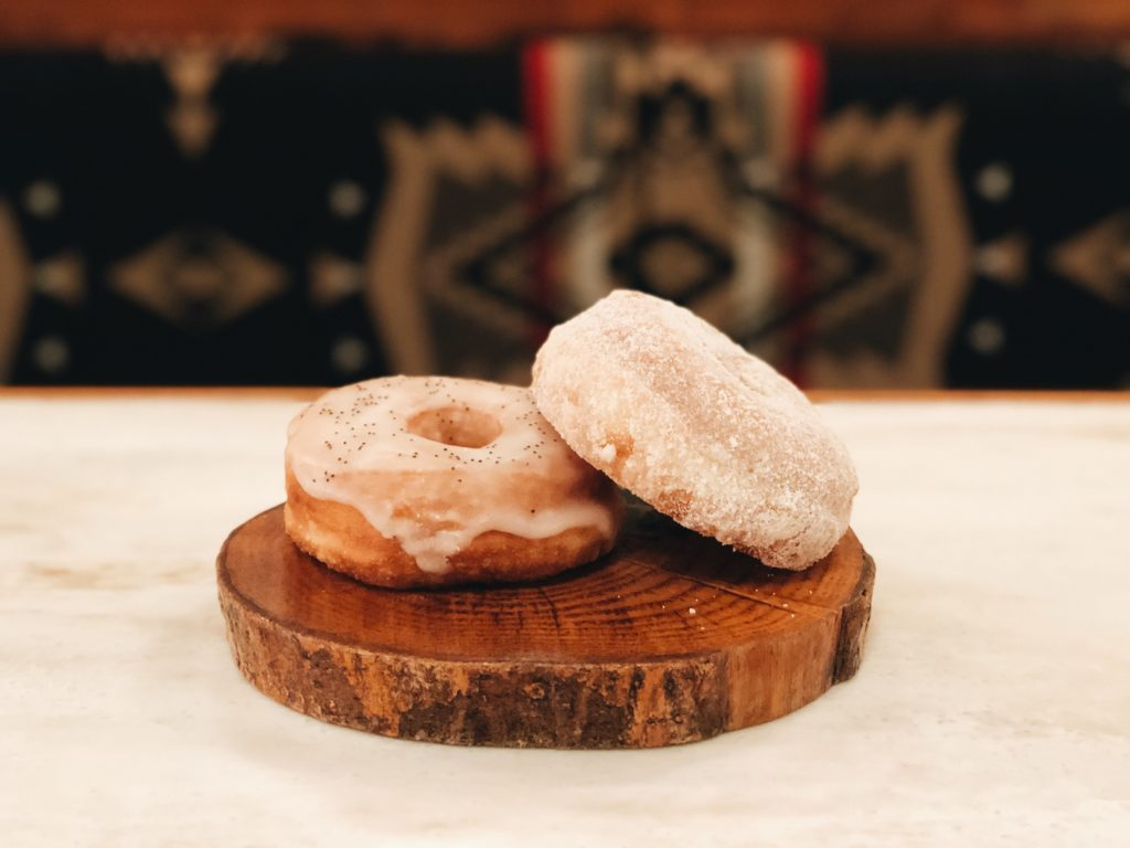 Two donuts stacked on a wood log platter.