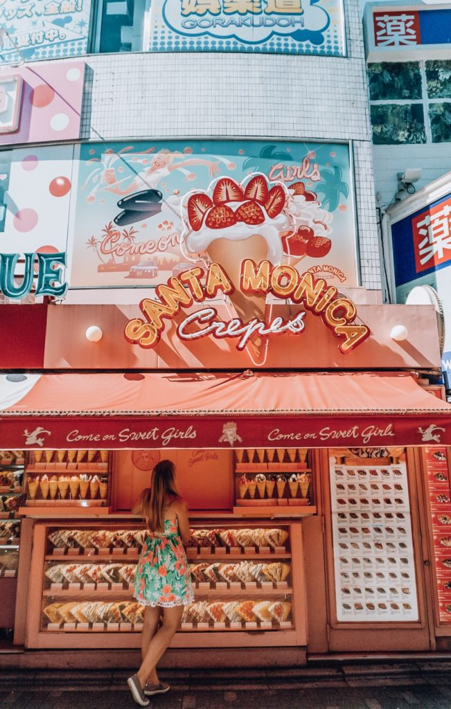 """Girl standing in front of a sweet crepe stand titled """"Santa Monica Crepes"""" in Harajuku, Japan"""