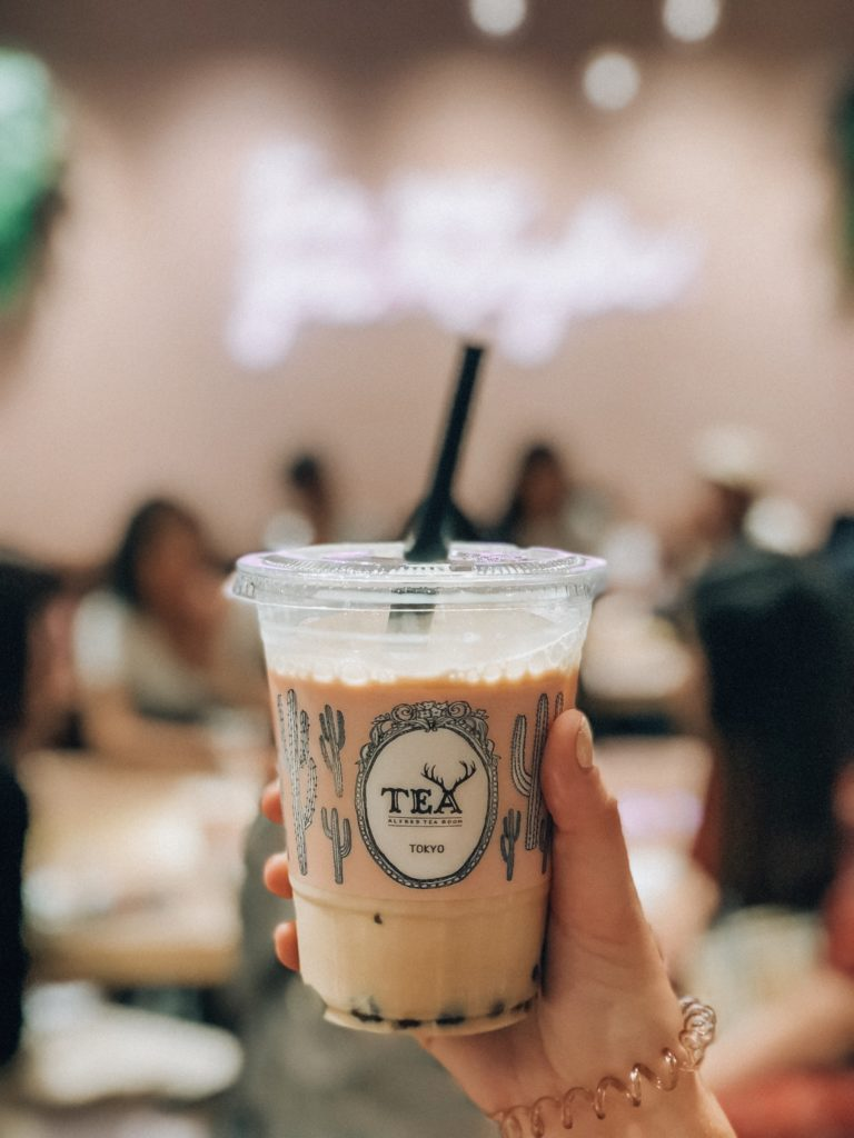 """Hand holding a plastic to-go cup that says """"TEA, TOKYO"""" inside is a boba drink from Alfred Tea"""