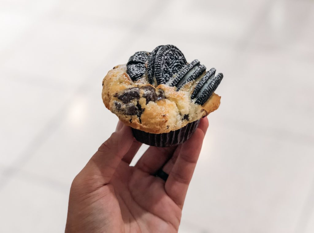 Hand holding a muffin with Oreo cookies
