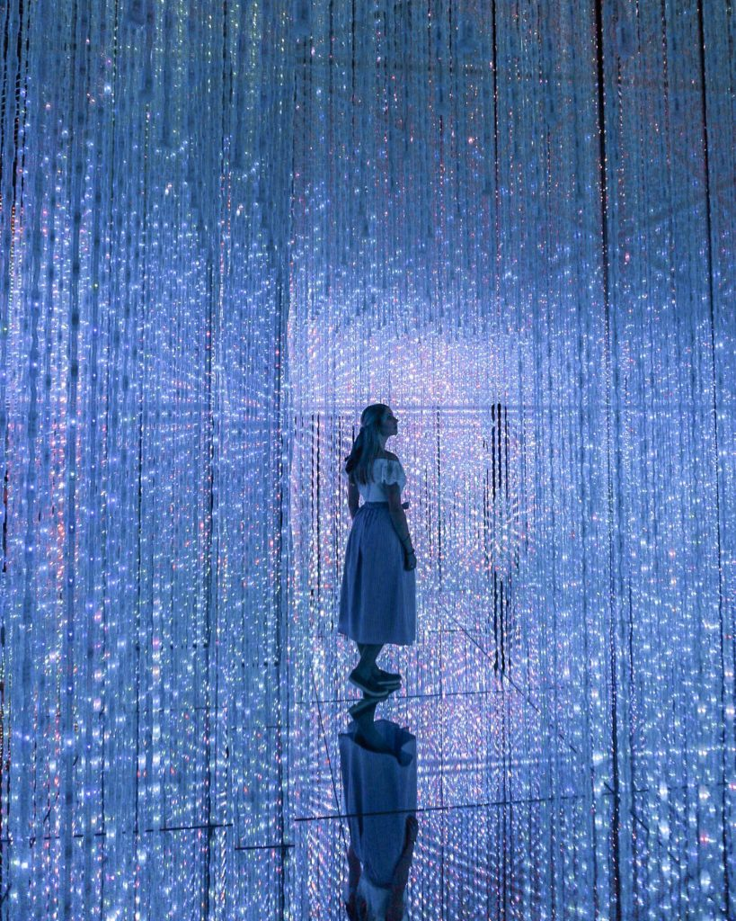 Girl standing in a room of blue lights from wall to ceiling - Mori Digital Art Museum Tokyo