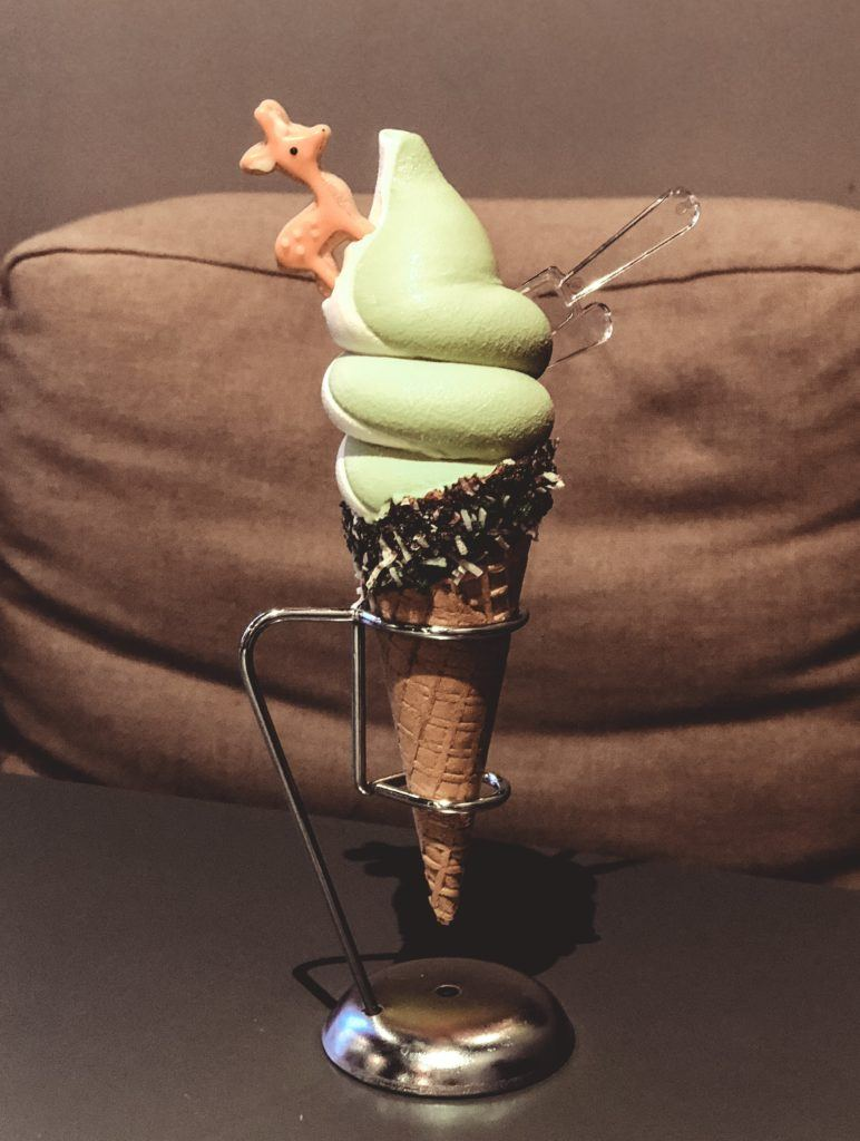 Ice cream cone with green tea and vanilla swirl ice cream and a biscuit shaped like a deer on top from Nara, Japan