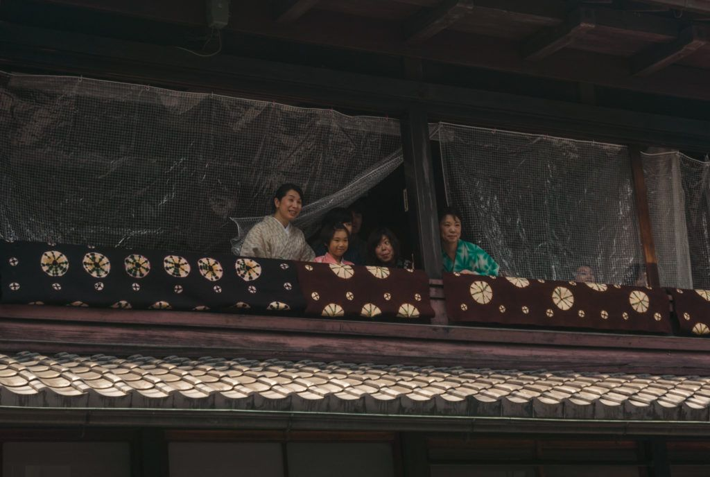 People waving from their home in Gion, Kyoto