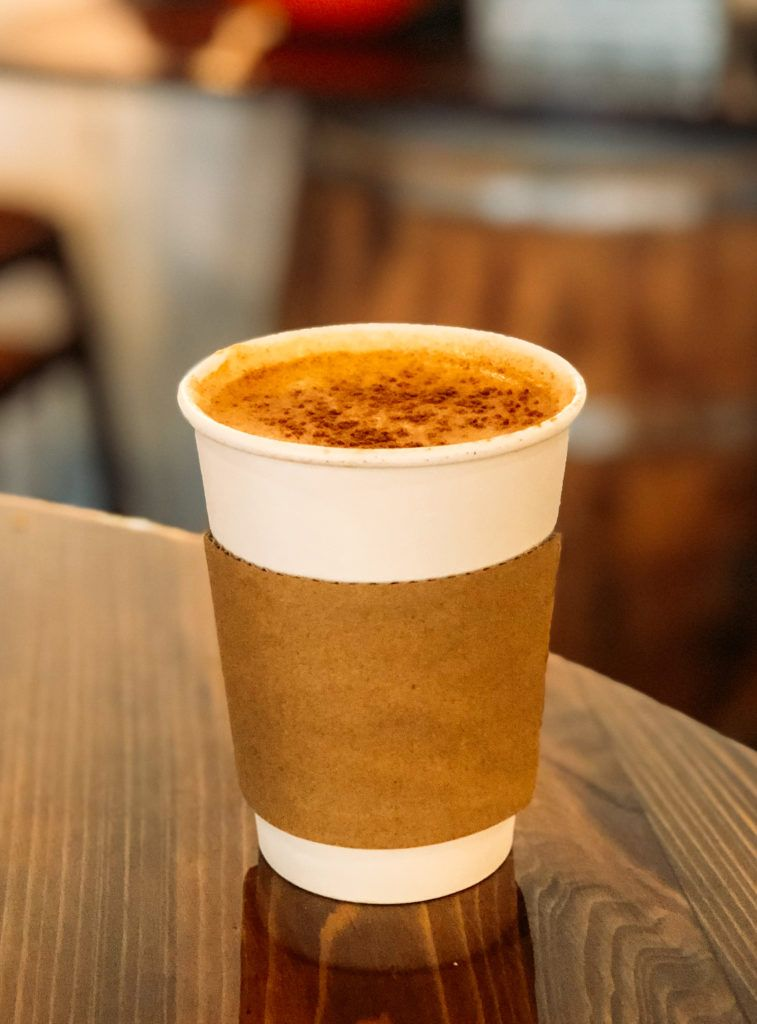 Latte in a to-go cup from Doomsday Coffee in Fayetteville