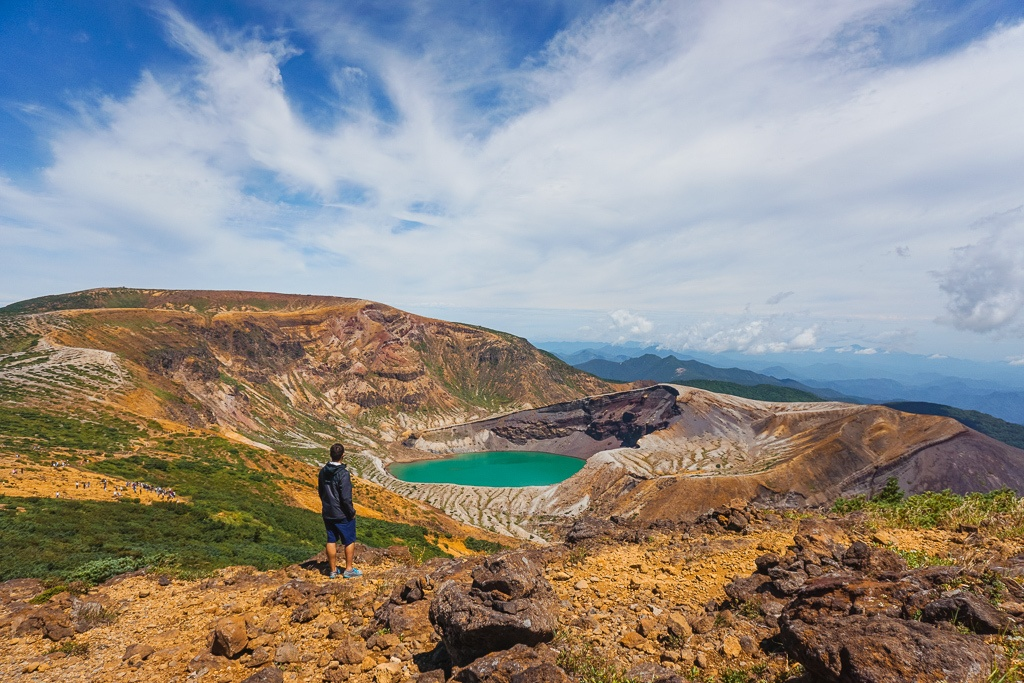Man with dark hair dressed in a black jacket and black shorts standing in front of Okama Crater from Mt. Zao in Japan.
