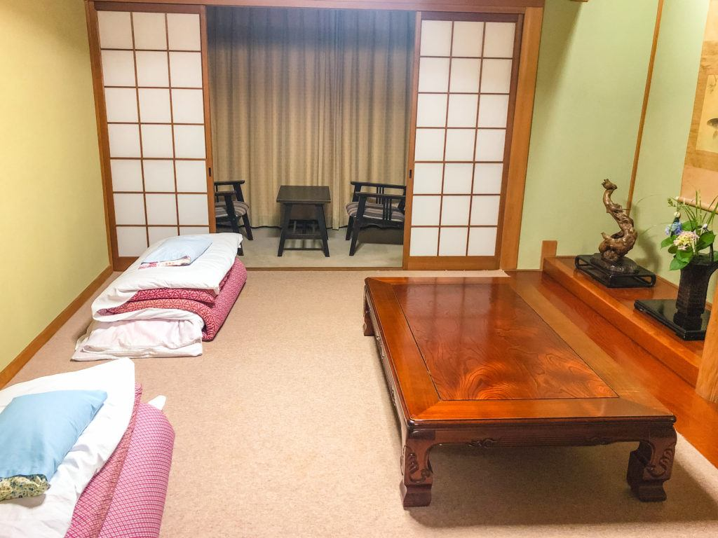 Room with two futons, a sitting area, and table at Yuhiken in Asago, Japan